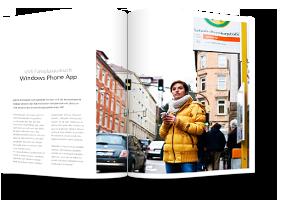 Frau mit einem Handy in der Hand wartet an einer VVS Haltestelle und schaut auf die Straße